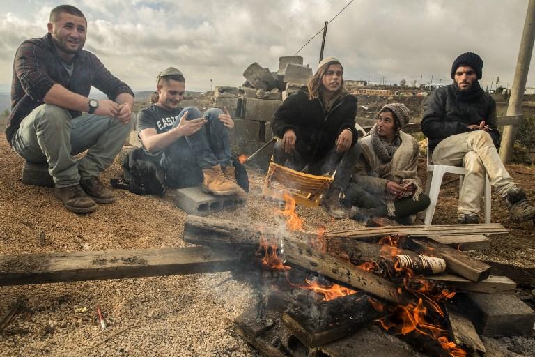 مستوطنون اسرائيليون في بؤرة عامونا الاستيطانية في الضفة الغربية، 18 ديسمبر 2016 (AFP /JACK GUEZ)