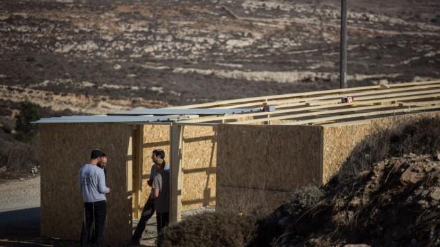 رجال يهود يبنون في بؤرة عامونا الاستيطانية في الضفة الغربية، 28 نوفمبر 2016 (Hadas Parush/Flash90)
