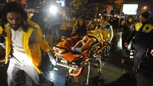 مسعفون يحملون امرأة مصابة في ساحة هجوم اطلاق نار في نادي ليلي في اسطنبول، 1 يناير 2017 (AFP/ IHLAS NEWS AGENCY)