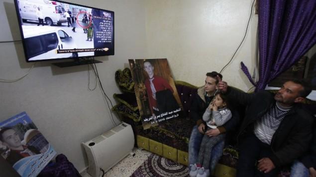 يسري، والد عبد الفتاح الشريف، يشاهد على التلفزيون الحكم في قضية الجندي الإسرائيلي ايلور عزاريا الذي قتل ابنه، في منزل العائلة بمدينة الخليل في الضفة الغربية، 4 يناير 2017 (AFP/HAZEM BADER)