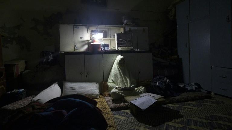 فتاة فلسطينية تحضر دروسها خلال انقطاع للكهرباء في غزة، 4 يناير 2017 (AFP/Mahmud Hams)