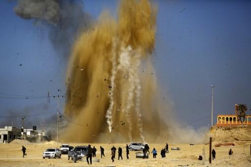 الفلسطينيون يبحثون عن مخبأ مع تصاعد الرمال والدخان في أعقاب غارة جوية إسرائيلية ضد موقع تابع لحركة 'حماس' شمال قطاع غزة، 6 فبراير، 2016. (Mohammed Abed/AFP)