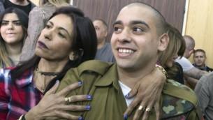 إيلور عزاريا يجلس إلى جانب والدته أوشرا  خلال حضوره لجلسة النطق بالحكم في المحكمة العسكرية في تل أبيب، 21 فبراير، 2017. (AFP/Pool/Jim Hollander)