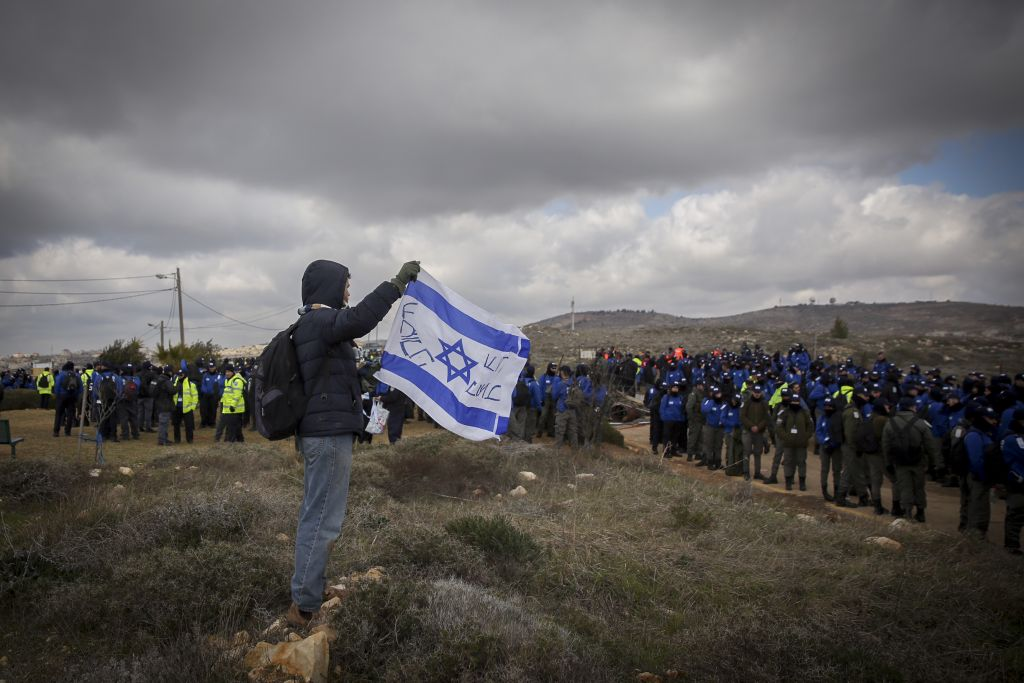 رجل يحمل علم اسرائيل امام عناصر الشرطة خلال عملية اخلاء بؤرة عامونا الاستيطانية في الضفة الغربية، 1 فبراير 2017 (Miriam Alster/Flash90)