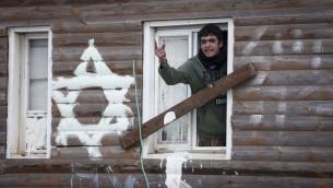 رجل يصرخ على الشرطة من داخل منزل خلال عملية اخلاء بؤرة عامونا الاستيطانية، 1 فبراير 2017 (Miriam Alster/Flash90)