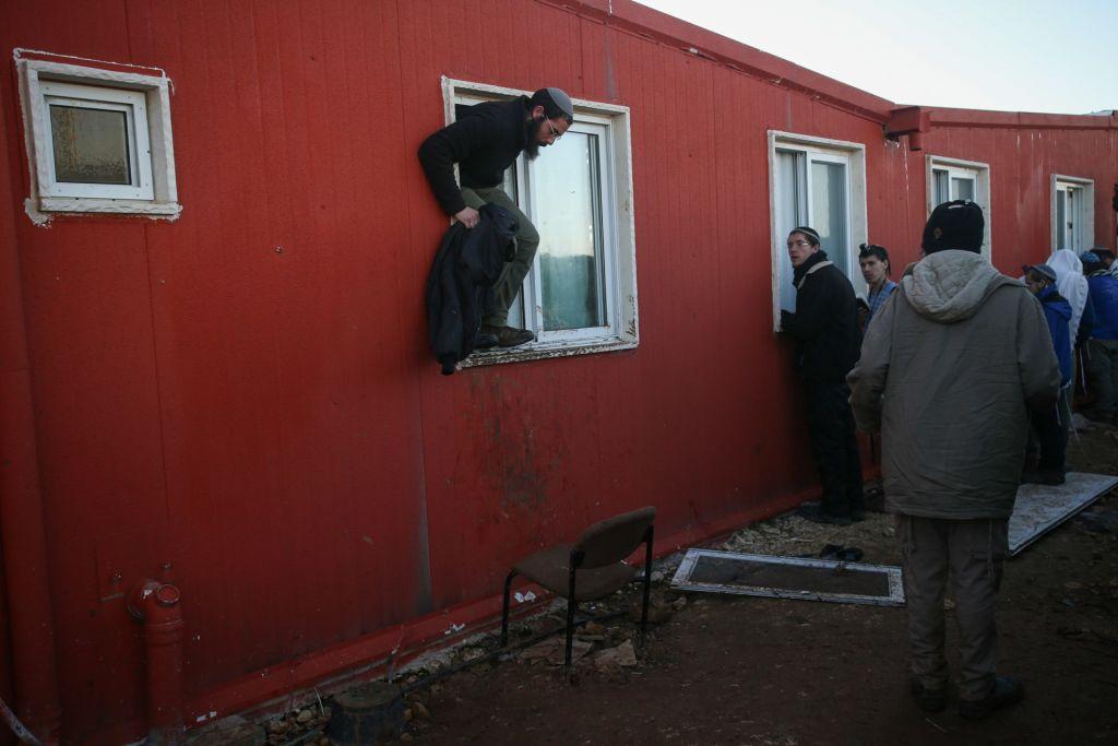 متظاهرون يحيطون بكنيس بؤرة عامونا الاستيطانية في اليوم الثاني لعملية اخلاء البؤرة، 2 فبراير 2017 (Yonatan Sindel/Flash90)