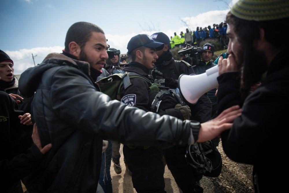 مستوطنون اسرائيليون يشتبكون مع قوات الامن خلال اخلاء بؤرة عامونا الاستيطانية في الضفة الغربية، 1 فبراير 2017 (Hadas Parush/Flash90)