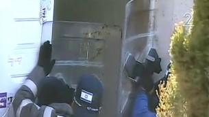 عناصر الشرطة يرفعون أدرعة بلاستيكية بينما يرشق المتظاهرون الزجاجات من داخل الكنيس في بؤرة عامونا الاستيطانية، 2 فبراير 2017 (Screen capture: Channel 2)