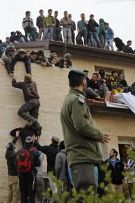 قوات الأمن الإسرائيلية تقف أمام أحد المنازل أحد المنازل المعدة للإخلاء والهدم في مستوطنة عوفرا في الضفة الغربية، بينما يأخذ نشطاء من اليمين مواقعهم على سطحه، 28 فبراير، 2017. (Menahem Kahana/AFP Photo)
