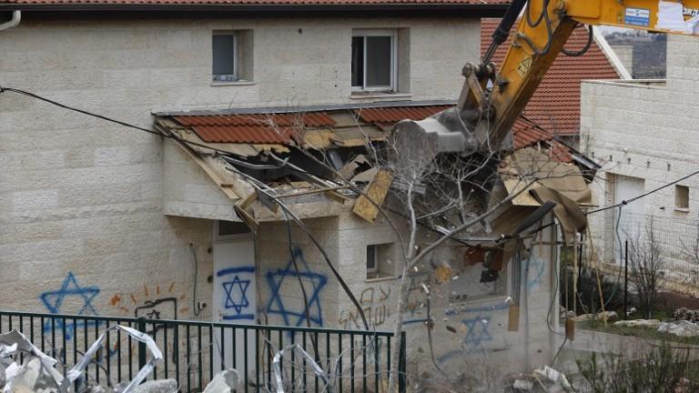 جرافة تهدم منزلا مبنيا على ارض فلسطينية خاصة في مستوطنة عوفرا بالضفة الغربية، 1 مارس 2017 (AFP Photo/Menahem Kahana)