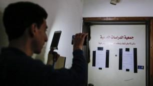 رجل يلتقط صورة بواسطة هاتفه الخليوي لاعلان يبلغ باغلاق مكتب مفترض في بيت حنينا بالقدس الشرقية لمدة ستة اشهر، 13 مارس 2017 (AFP Photo/Ahmad Gharabli)