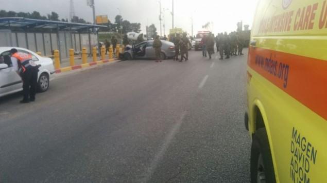 جنود يحيطون بمركبة اصطدمت بمحطة حافلات في ما يٌشتبه بأنه هجوم دهس في مفرق عتصيون في الضفة الغربية، 15 مارس، 2017 (Magen David Adom)