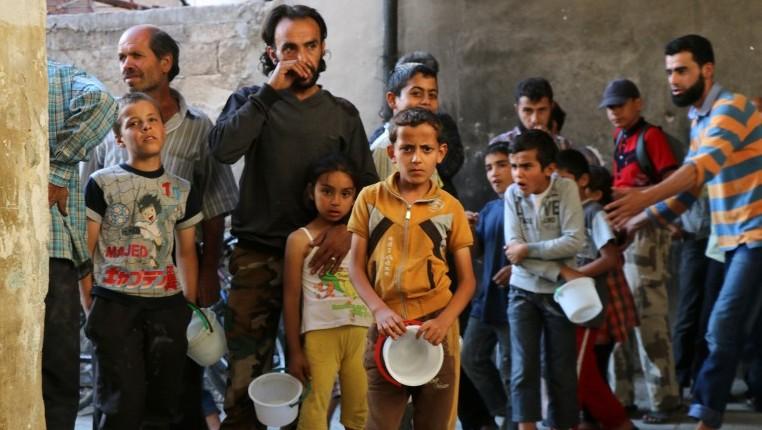 سوريون ينتظرون الحصول على الطعام من قبل جمعية خيرية خلال شهر رمضان في حي تسيطر عليه المعارضة في حلب، 11 يونيو 2016 (AFP/THAER MOHAMMED)