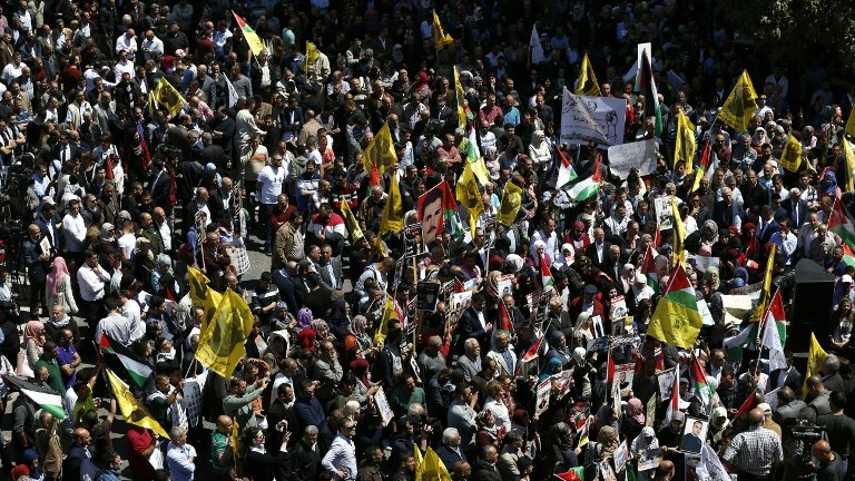 متظاهرون يحملون صور اسرى فلسطينيين خلال مظاهرة في رام الله دعما للاسرى الفلسطينيين المضربين عن الطعام في السجون الإسرائيلية، 17 ابريل 2017 (AFP Photo/Abbas Momani)