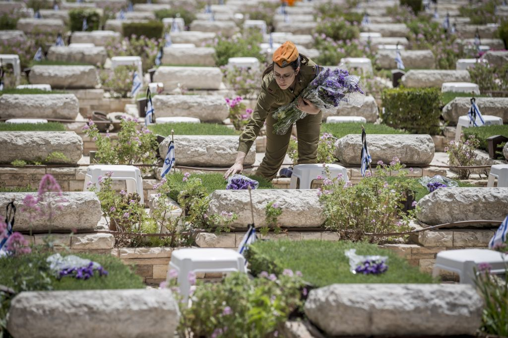 جنود اسرائيليون يضعون الزهور على قبور الجنود المقتلوين في الحروبات في مقبرة جبل هرتسل العسكرية في القدس، 30 ابريل 2017 (Yonatan Sindel/Flash90)