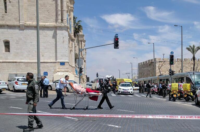 مسعفون ينقلون مصابة في ساحة هجوم طعن في القطار الخفيف في القدس، 14 ابريل 2017 (Magen David Adom)