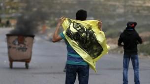 متظاهر فلسطيني يحمل علم عليه صورة مروان البرغوثي خلال مظاهرة في الضفة الغربية، 23 ابريل 2017 (AFP Photo/Abbas Momani)