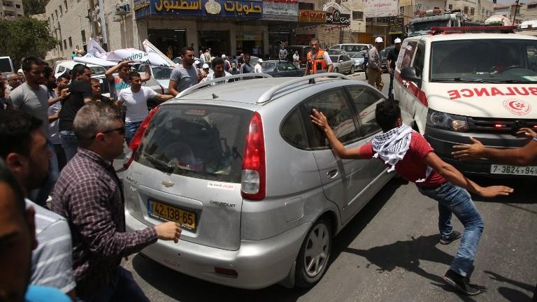 متظاهرون فلسطينيون يحيطون بسيارة مستوطن اسرائيلي حاول المرور وسط مظاهرة بالقرب من حاجز حوارة العسكري في شمال الضفة الغربية، 18 مايو 2017 (AFP Photo/Jaafar Ashtiyeh)