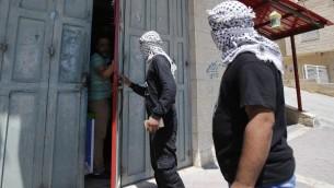 ناشطون في حركة فتح يتحدثون مع صاحب متجر بينما يجولون في شوارع مدينة بيت لحم لمراقبة تطبيق الاضراب العام الذي نادى اليه ناضطون في انخاء الاراضي الفلسطينية والعرب في اسرائيل، دعما للاشرى الفلسطينيين المضربين عن الطعام في السجون الإسرائيلية، 22 مايو 2017 (AFP/Musa AL SHAER)