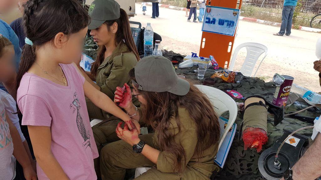 جنود من كتيبة عتصيون يرسموا جراح مزيفة على اطفال، في مستوطنة تكوع ضمن عرض للجيش في يوم الاستقلال، 2 مايو 2017 (Courtesy)