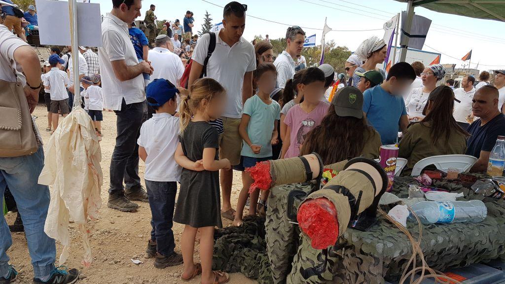 جنود من كتيبة عتصيون يرسموا جراح مزيفة على اطفال، امام اقدام مصطنعة مقطوعة، في مستوطنة تكوع ضمن عرض للجيش في يوم الاستقلال، 2 مايو 2017 (Courtesy)