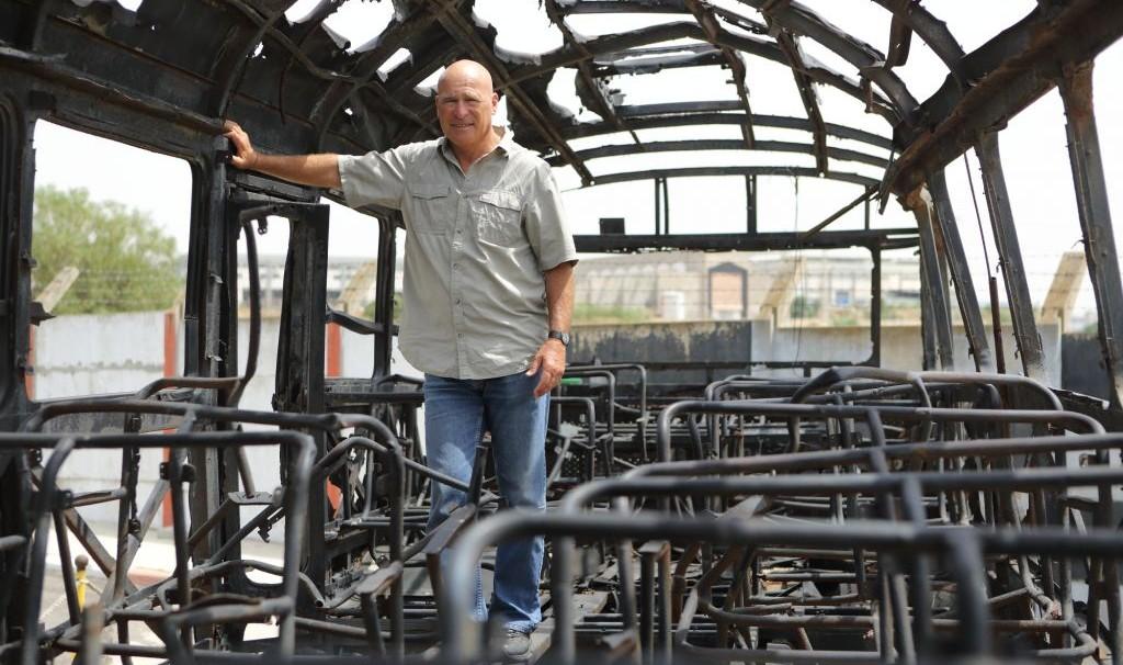 مفوض الشرطة الإسرائيلية السابق اساف حيفيتس داخل حافلة من اعتداء عام 1978 المعروف باسم مجزرة شارع الشاطئ، في متحف في حولون، 2 مايو 2013 (Yaakov Naumi/Flash90)