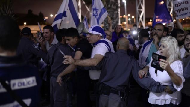إسرائيليون يتظاهرون ضد المراسم التذكارية لضحايا الصراع الإسرائيلي-الفلسطيني في تل أبيب، 30 أبريل، 20017، في اليوم الذي تحيي فيه إسرائيل يوم ذكرى القتلى من جنودها والمدنيين ضحايا الهجمات. (Tomer Neuberg/Flash90)