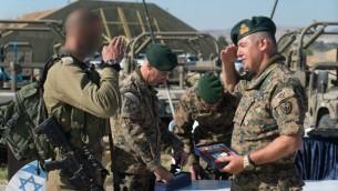 جندي قبرصي يحيي جندي اسرائيلي خلال تدريب عسكري في قبرص، يونيو 2017 (IDF Spokesperson's Unit)