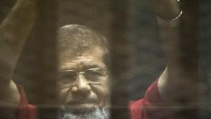 ارشيف - الرئيس المصري المخلوع محمد مرسي داخل قفص خلال محاكمته في القاهرة، 7 مايو 2016 (AFP PHOTO/KHALED DESOUKI)