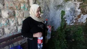 امرأة من عائلة سليم تحمل مياه نبع في سلفيت، شمال رام الله، 23 يونيو 2016 (AFP/Jaafar Ashtiyeh)