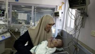 جمانة داوود من غزة تحمل ابنتها مريم البالغة من العمر 7 أشهر في مستشفى مقاصد في القدس الشرقية في 20 فبراير 2017، لأنها تجتمع بها لأول مرة منذ ولادة الطفلة المبكرة. (AFP/AHMAD GHARABLI).