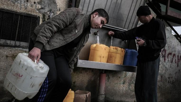 فلسطينيون يملأون اوعية بمياه الشرب من حنفيات عمومية في مخيم رفح، جنوب غزة، 22 فبراير 2017 (Said Khatib/AFP)