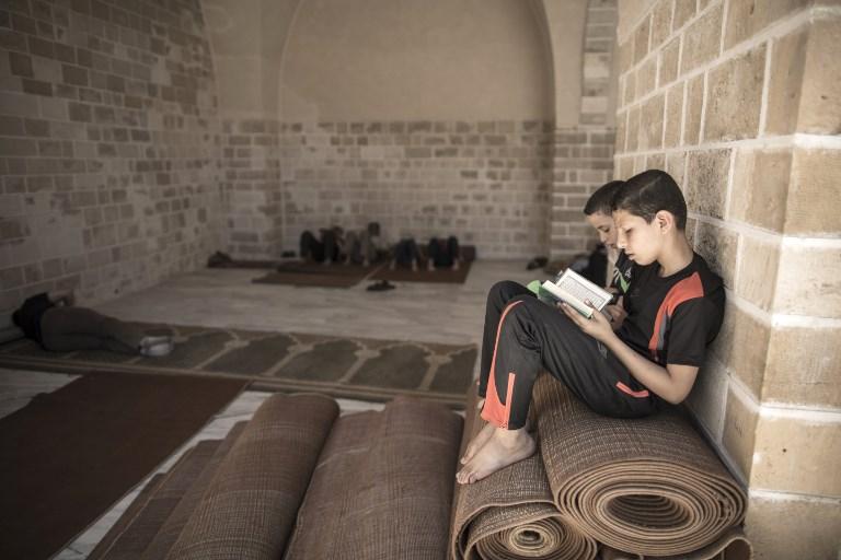 اطفال فلسطينيون يقرأون القرآن في اول يوم رمضان، في مسجد العمري في غزة، 27 مايو 2017 (AFP PHOTO / Mahmud Hams)