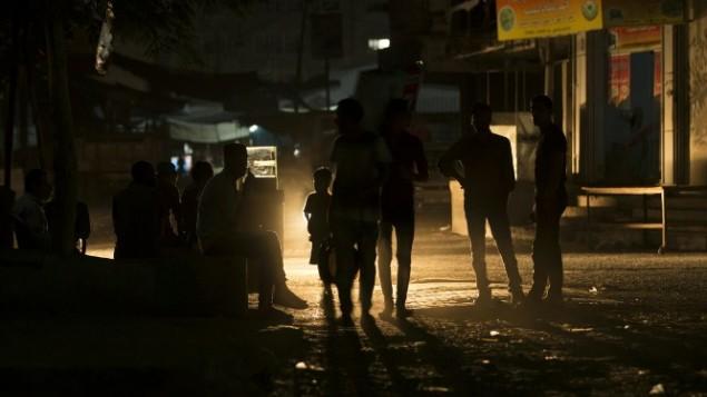 فلسطينيون يسيرون في شارع مظلم أثناء انقطاع التيار الكهربائي في مخيم الشاطئ للاجئين في مدينة غزة، 11 حزيران 2017. (AFP/Mahmud Hams)