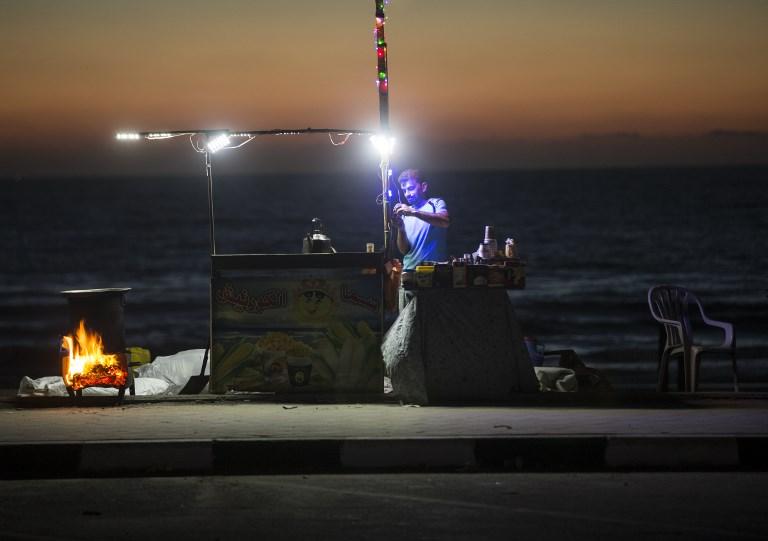 بائع فلسطيني انان شاطئ غزة خلال انقطاع للكهرباء، 11 يونيو 2017 (AFP/MAHMUD HAMS)