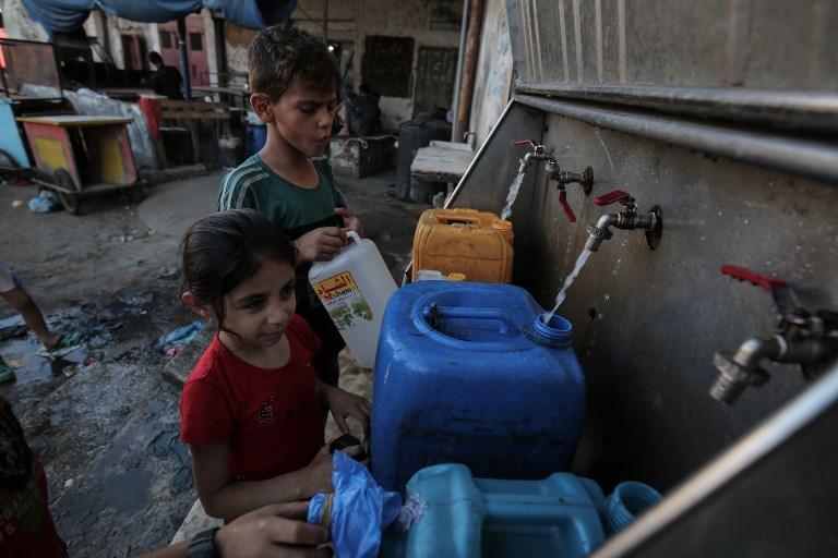 اطفال فلسطينيون يملأون اوعية بمياه الشرب من حنفيات عمومية في جنوب قطاع غزة، 11 يونيو 2017 (AFP/SAID KHATIB)