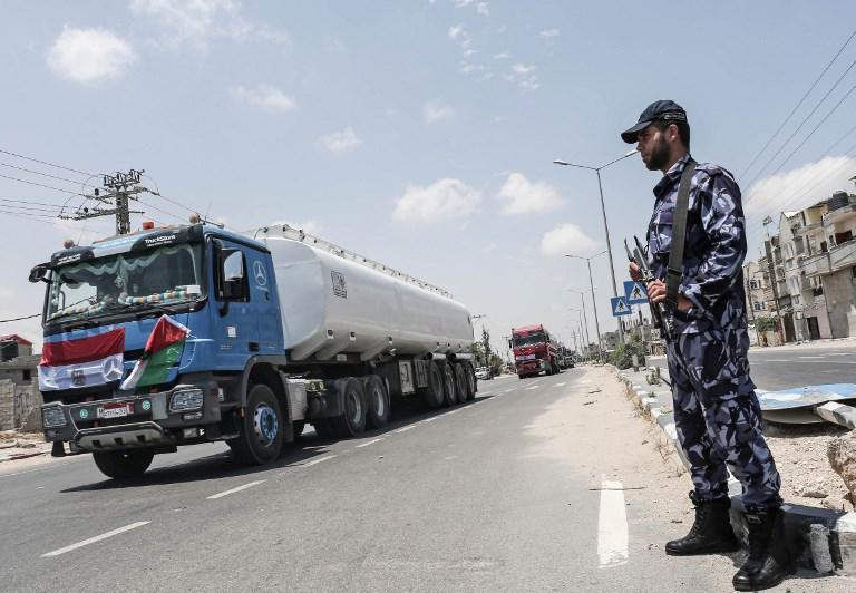 قوات الأمن الفلسطينية تقف لحراسة الشاحنات المصرية التي تنقل الوقود إلى الشارع بعد دخولها إلى جنوب قطاع غزة من مصر عبر معبر رفح الحدودي في 21 يونيو / حزيران 2017. (AFP PHOTO / SAID KHATIB)