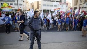 رجل شرطة إسرائيلي يقف حارسا في حين يشارك الإسرائيليين في موكب الفخر السنوي الأول في مدينة بئر السبع جنوب إسرائيل، في 22 يونيو / حزيران 2017. (AFP/Menahem Kahana)