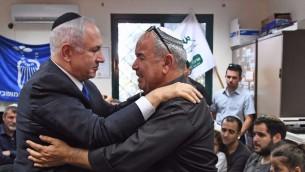 رئيس الوزراء بنيامين نتنياهو يعانق ديفيد مالكا، والد ضابطة شرطة الحدود المقتولة هداس مالكا في 18 يونيو 2017. (Koby Gideon/GPO)