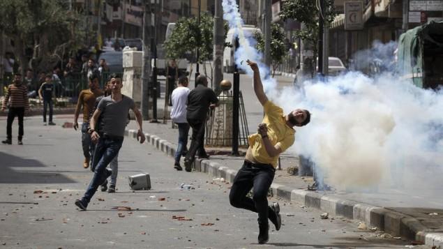 فلسطينيون يرشقون الحجارة باتجاه جنود اسرائيليين خلال اشتباكات في مدينة الخليل في الضفة الغربية، 27 ابريل 2017 (Wisam Hashlamoun/Flash90)