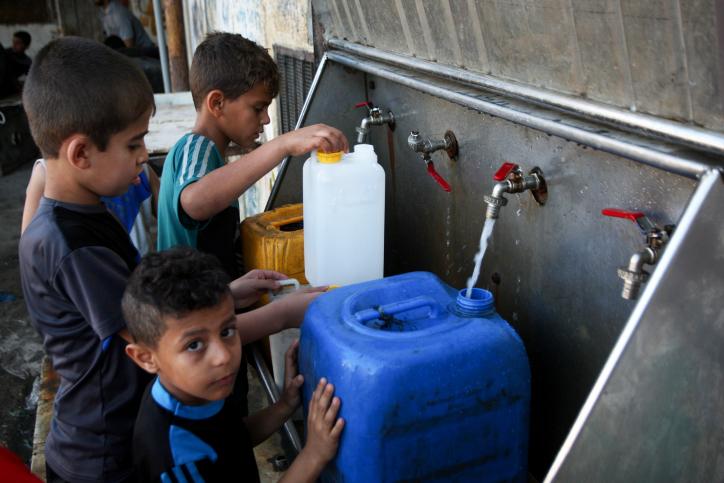 اطفال فلسطينيون يملأون اوعية بمياه الشرب من حنفيات عمومية في جنوب قطاع غزة، 11 يونيو 2017 (Abed Rahim Khatib/Flash90)