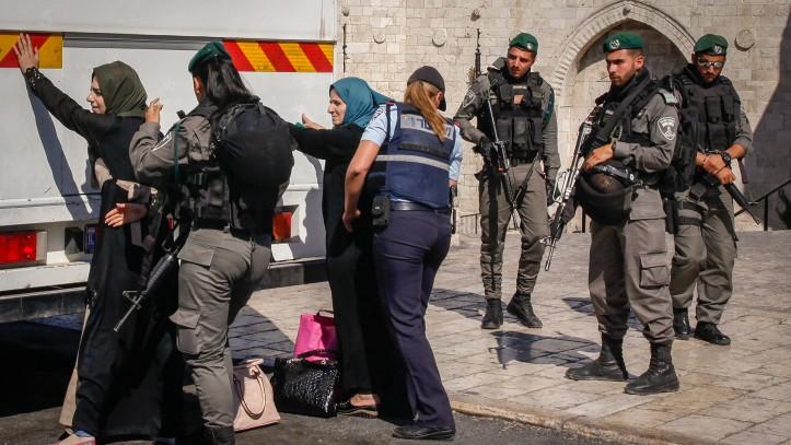 عناصر قوات امن اسرائيليين يفتشون نساء فلسطينيان امام باب العامود في القدس القديمة، قبل السماح لهن الصعود على متن حافلة متجهة الى الضفة الغربية، 17 يونيو 2017 (Sliman Khader/Flash90)