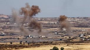 صورة تم إلتقاطها من الجانب الإسرائيلي من الحدود تظهر الدخان المتصاعد من الحدود الإسرائيلية السورية في هضبة الجولان خلال معارك بين المتمردين والجيش السوري داخل سوريا، 25 يونيو، 2017. (Basel Awidat/Flash90)