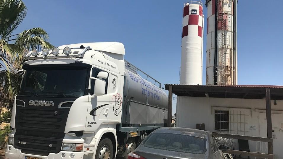 شاحنة تملأ برج المياه في مستوطنة ميغداليم في شمال الضفة الغربية، 4 يونيو 2017 (Jacob Magid/Times of Israel)