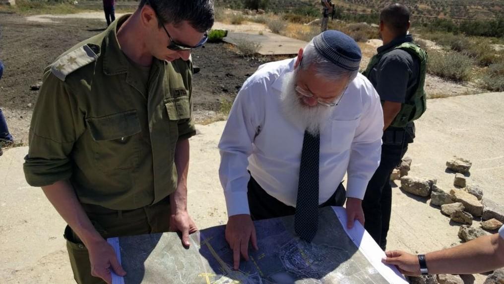 نائب وزير الدفاع ايلي بن داهان يتحدث مع مسؤول في الادارة المدنية في الجيش الإسرائيلي خلال جولة عمل في انبوب المياه في مفترق تابوح، 19 مايو 2017 (Courtesy: Eli Ben Dahan)