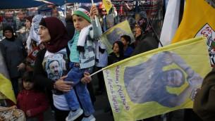 فلسطينيون يحملون أعلام تحمب صورة الأسير الفلسطيني مروان البرغوثي خلال تظاهرة في مدينة رام الله في الضفة الغربية دعما للأسرى المضربين عن الطعام، 24 أبريل، 2017. (AFP Photo/Abbas Momani)