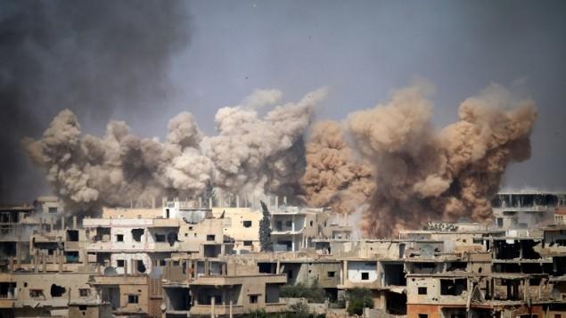 الدخان يتصاعد من مبان في أعقاب غارة جوية على منطقة يسيطر عليها المتمردون في مدينة درعا، جنوب سوريا، 14 يونيو، 2017. (AFP/Mohamad Abazeed)