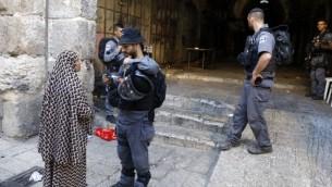 شرطي من حرس الحدود يقوم بالتحقق نت بطاقة هوية سيدة فلسطينية في البلدة القديمة في القدس، 16 يوليو، 2017. (Menahem Kahana/AFP)
