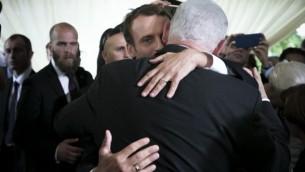 الرئيس الفرنسي ايمانويل ماكرون يحتضن رئيس الوزراء الاسرائيلي بنيامين نتانياهو خلال احتفالات الذكرى السنوية ال 75 لجولة فيلودروم دي هايف في باريس في 16 تموز / يوليو 2017. (AFP/Pool/Kamil Zihnioglu)