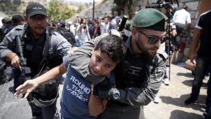 شرطيان من حرس الحدود الإسرائيلي يعتقلان فتى فلسطينيا خلال تظاهرة أمام باب الأسباط في البلدة القديمة في القدس، 17 يوليو، 2017. (AFP/AHMAD GHARABLI)
